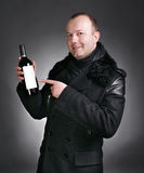 Man with bottle of wine. Handsome young man in winter coat with a bottle of wine on a gray background stock photography