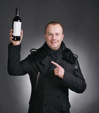 Man with bottle of wine. Handsome young man in winter coat with a bottle of wine on a gray background Stock Photos