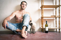 Man with a bottle of wine and cat. Sitting on a floor Stock Photography