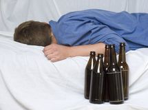 Man and Bottles. Man sleeping, beer bottles next to the bed Royalty Free Stock Photography