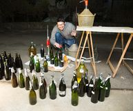 Man bottling red wine from the demijohn to glass bottles Royalty Free Stock Photos
