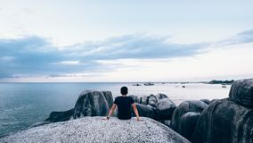 Man on boulder overlooking ocean Royalty Free Stock Photos