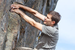 Man bouldering. Handsome young man bouldering or rock climbing outdoors Stock Photo