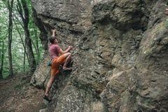 Man bouldering on stone rock Stock Photos