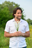 Man with a bouquet of daisies on the meadow Stock Photo