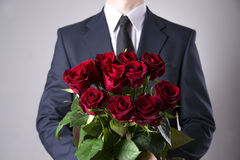 Man with bouquet of red roses on a gray background. Present at the International Women's Day Royalty Free Stock Photography
