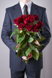 Man with bouquet of red roses on a gray background. Present at the International Women's Day Royalty Free Stock Photo