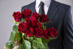 Man with bouquet of red roses on a gray background. Present at the International Women's Day Stock Images