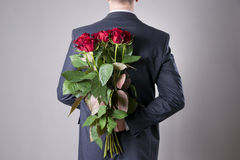 Man with bouquet of red roses on a gray background. Present at the International Women's Day Stock Photography