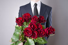 Man with bouquet of red roses on a gray background. Present at the International Women's Day Royalty Free Stock Images