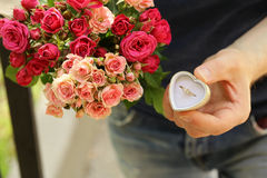 Man with a bouquet of roses and a diamond ring Stock Photos