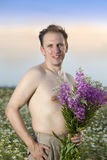 The man with a bouquet of wild flowers in the field Royalty Free Stock Photos