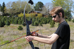 Man with bow and arrow. Young adult man getting his bow and arrow ready for archery Royalty Free Stock Image