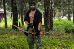 Man With A Bow And Arrows In Woods Stock Photography