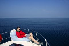 Man on bow boat relaxed on bean bag. Over blue sea stock photos