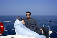 Man on bow boat relaxed on bean bag. Over blue sea royalty free stock photos