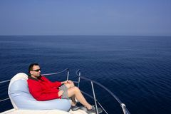 Man on bow boat relaxed on bean bag. Over blue sea stock image