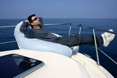 Man on bow boat relaxed on bean bag. Over blue sea stock photo