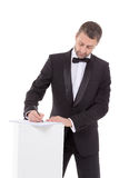 Man in a bow tie completing a form Royalty Free Stock Photography