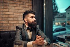 Man in a bow tie. Confident bar customer sit in cafe and thinking. Date meeting of hipster awaiting in pub. Business on Royalty Free Stock Photos