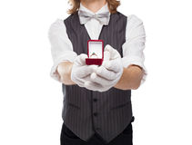 Man in a bow tie holds out box with the ring Royalty Free Stock Photo