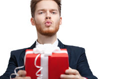 Man in bow tie offers a present and blows a kiss Royalty Free Stock Image