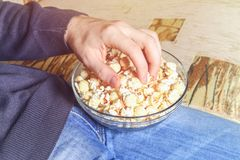 A man with a bowl of popcorn in his hand is watching TV on the sofa. A man with a bowl of popcorn in his hand is watching TV on the sofa Stock Image