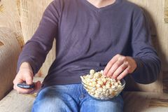 A man with a bowl of popcorn and a remote control in his hand looks at the TV on the sofa. A man with a bowl of popcorn and a remote control in his hand looks Royalty Free Stock Images