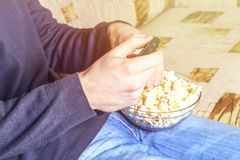A man with a bowl of popcorn and a remote control in his hand looks at the TV on the sofa. A man with a bowl of popcorn and a remote control in his hand looks Royalty Free Stock Photography