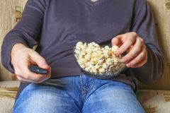 A man with a bowl of popcorn and a remote control in his hand looks at the TV on the sofa. A man with a bowl of popcorn and a remote control in his hand looks Stock Images