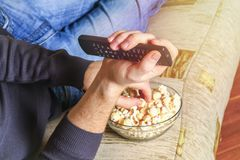 A man with a bowl of popcorn and a remote control in his hand looks at the TV on the sofa. A man with a bowl of popcorn and a remote control in his hand looks Stock Photography