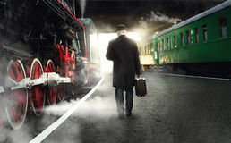 Man in bowler hat with suitcase walking on the platform next to. Rear view of man in bowler hat with suitcase walking on the platform next to steaming locomotive stock photos