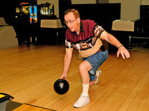Man Bowling. Front view of a man releasing ball at the foul line Royalty Free Stock Image