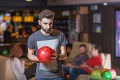 Man with bowling ball. Young bearded men with bowling ball concentrating Royalty Free Stock Photography