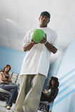 Man Bowling With Female Friends In Background Royalty Free Stock Images