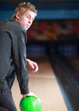Man on bowling lane. A young man kneeling with a green bowling ball and looking over his shoulder at a bowling lane Stock Image