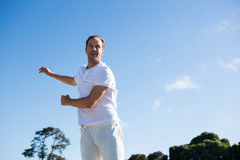 Man bowling while standing on cricket field. Against sky Royalty Free Stock Images
