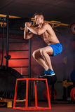 Man box jumping at a crossfit style gym. Stock Images