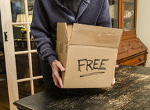 Man with box marked free Stock Image