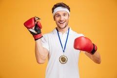 Man boxaren i röda handskar och hållande trofékopp för medalj royaltyfria bilder