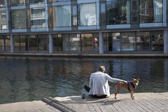 The man with the boxer dog sitting on the Regent Canal waterfron Stock Images