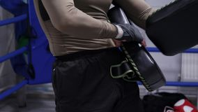 Man boxer putting boxing pads for personal training with partner. Professional boxer using kick pads on boxing ring. MMA. Training. Boxing training in gym stock video