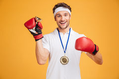 Man boxer in red gloves and medal holding trophy cup. Cheerful successful young man boxer in red gloves and medal holding trophy cup over yellow background Royalty Free Stock Images