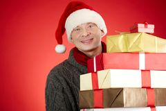 Man with boxes. Portrait of happy man in Santa cap with stack of giftboxes looking at camera Royalty Free Stock Photo