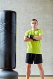 Man with boxing gloves and punching bag in gym Royalty Free Stock Images