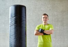 Man with boxing gloves and punching bag in gym Stock Images
