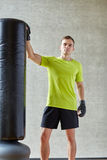 Man with boxing gloves and punching bag in gym Stock Image