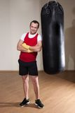 Man in boxing gloves with punching bag Stock Image