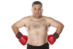 Man with boxing gloves. Serious and frown fat man with boxing gloves Royalty Free Stock Photo