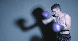 Man in boxing gloves. Shows the different movements and strikes in the studio. Fog in the background stock footage